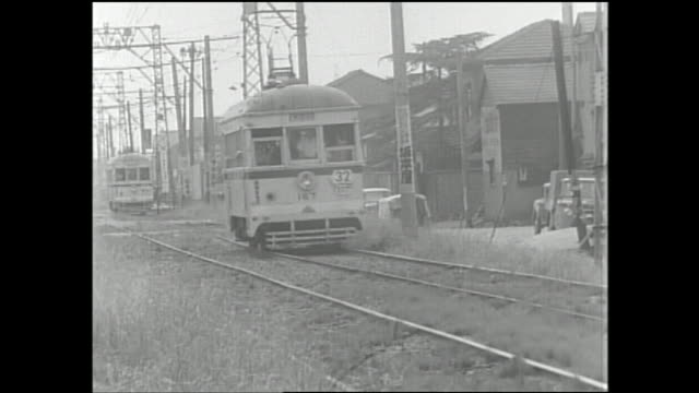 a toei streetcar travels along a dedicated track. - postwar stock videos & royalty-free footage