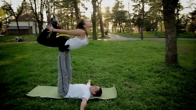 stockvideo's en b-roll-footage met samen beoefenen van yoga, buitenshuis - acrobaat