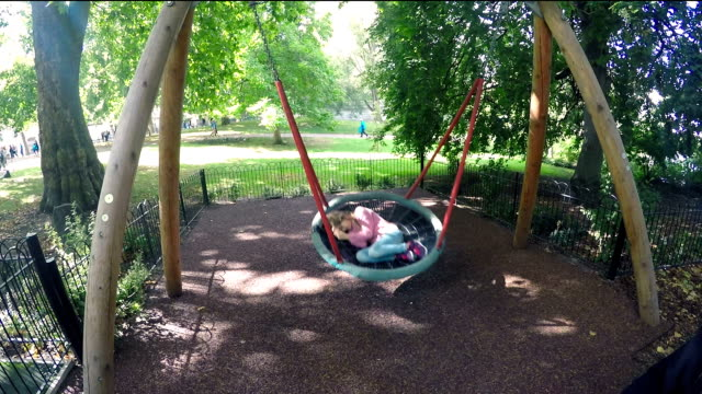 Togetherness. Preteen girl enjoying a relaxing time on a swing while her father swings her