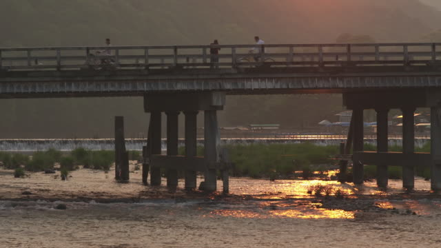 vídeos de stock e filmes b-roll de togetsukyo bridge over katsura river in kyoto during the sunset - 50 segundos ou mais