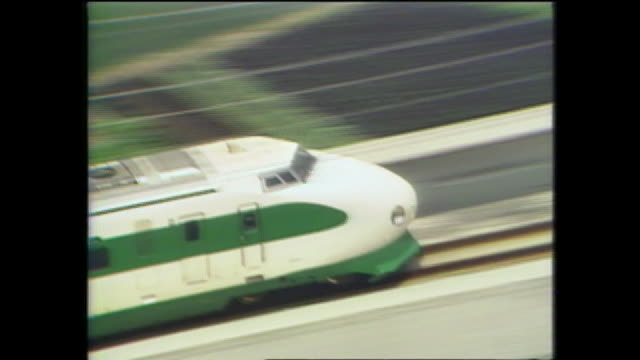 A Tohoku Shinkansen bullet train locomotive speeds through the Japanese countryside on opening day