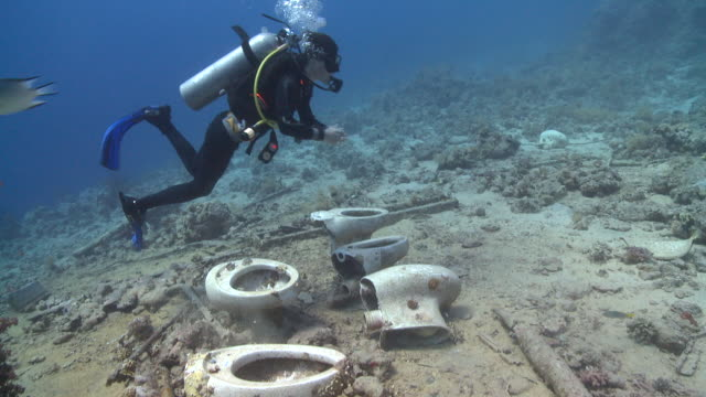 Toilet bowls on sea floor by wreck of Thistlegorm; diver leaves them, Antarctica