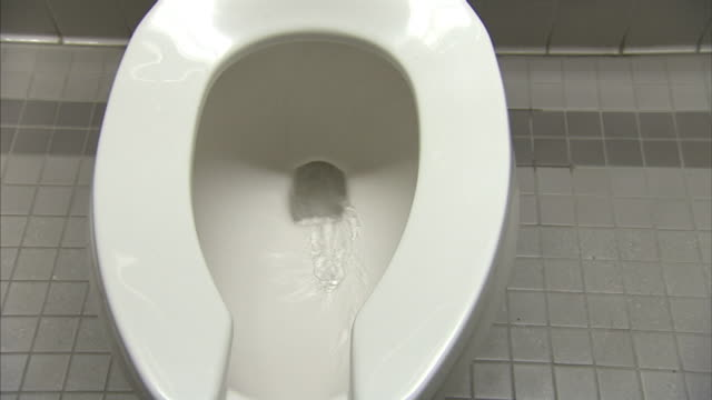 vídeos y material grabado en eventos de stock de a toilet in a public bathroom flushes automatically. - baño
