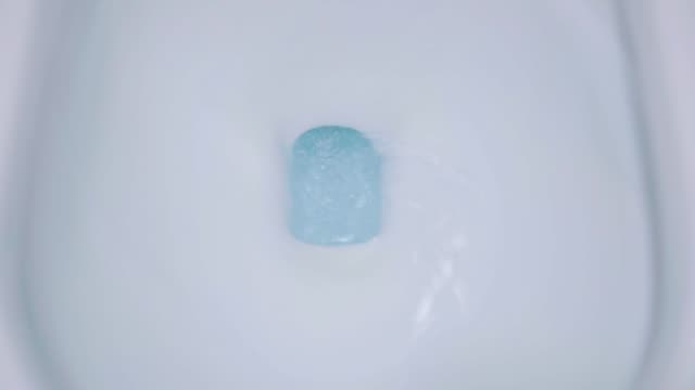 vidéos et rushes de toilette avec l'eau bleue dans le rinçage de cuvette - bol vide