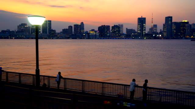 vídeos de stock, filmes e b-roll de baía de tóquio e ponte arco-íris ao anoitecer. pescando fora do parque. - porto distrito