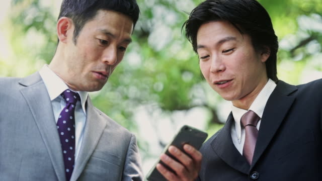 tokyo businessmen looking at phone - 歯を見せて笑う点の映像素材/bロール