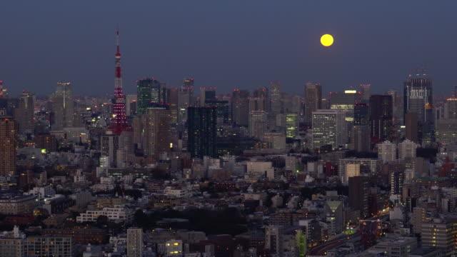 vídeos de stock, filmes e b-roll de arquitectura da cidade de tokyo-lua que levanta-se acima dos arranha céus - meia noite