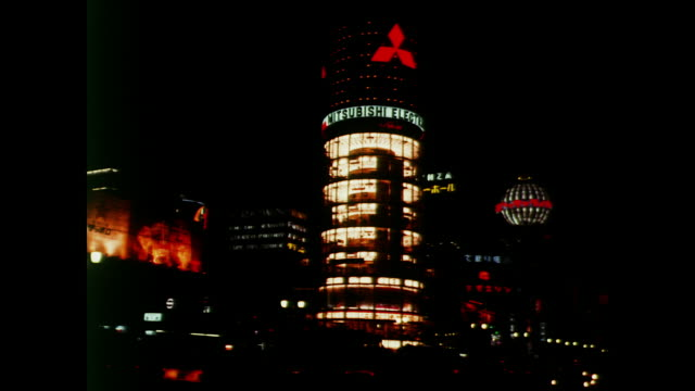 1964 tokyo, dot matrix light pattern runs through its sequence on the nec electronics building at night followed by the lighted top of the mitsubishi electronics building - 1964年点の映像素材/bロール