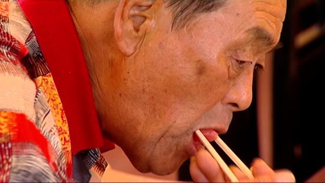 vídeos de stock e filmes b-roll de tokyo int chef carrying along large bluefin tuna fish through sushi restaurant chef gutting bluefin tuna fish japanese man eating raw tuna fish with... - amanhar o peixe