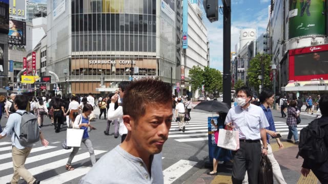 stockvideo's en b-roll-footage met tokyo is home to the shibuya crossing, which is the busiest pedestrian crossing in the world. at shibuya crossing, approximately 2,500 pedestrians... - shibuya shibuya station