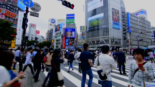 stockvideo's en b-roll-footage met tokyo japan crowds rush moving walking in the busy shibuya station area of shilbuya crossing with locals rushing everywhere in downtown crowded streets and sidewalks crossing - shibuya shibuya station