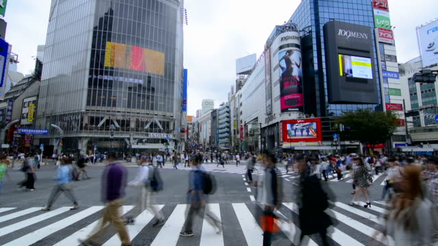 tokyo japan crowds rush moving walking in the busy shibuya station area of shilbuya crossing with locals rushing everywhere in downtown crowded streets and sidewalks crossing - poster stock videos and b-roll footage