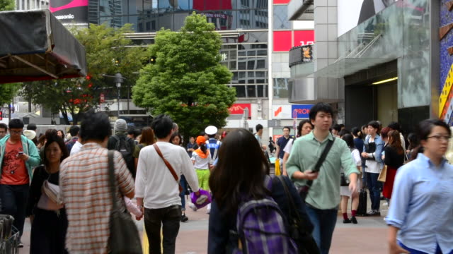 tokyo japan crowds rush moving walking in the busy shibuya station area of shilbuya crossing with locals rushing everywhere in downtown crowded streets and sidewalks crossing - 日本語の文字点の映像素材/bロール
