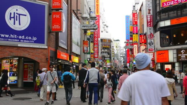 tokyo japan crowds walking near restaurants  in shibuya station area of shilbuya crossing with colorful signs  and rush crowds in street - setting stock videos & royalty-free footage
