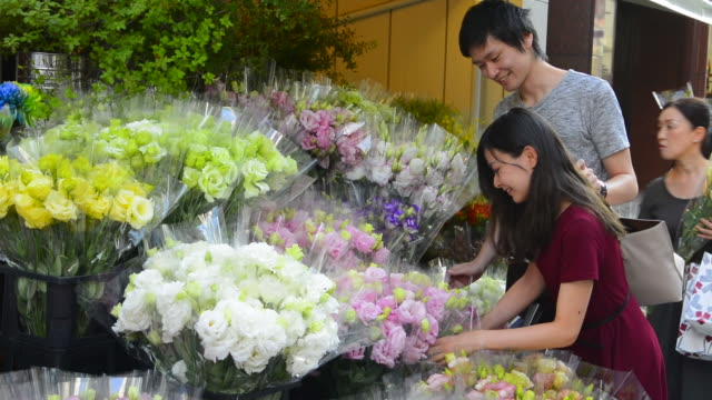 tokyo japan ginza shopping street couple buying beautiful flowers from shop on exclusive ginza street the main street for shopping in tokyo - florist stock videos & royalty-free footage