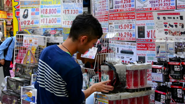 Tokyo Japan modern high tech area called Akihabara area man looking to buy computer hard drives and items and cartoon type games called Electric Town video games