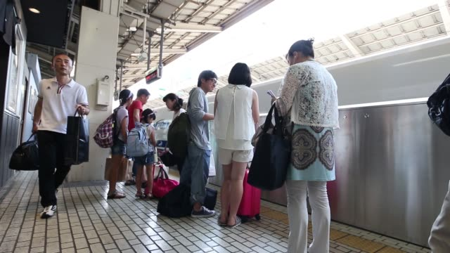 Tokyo Japan on Wednesday Aug 12 2015 Shots Wide shot travelers walk through Tokyo Station in Tokyo Passengers wait to board a bullet train at Tokyo...