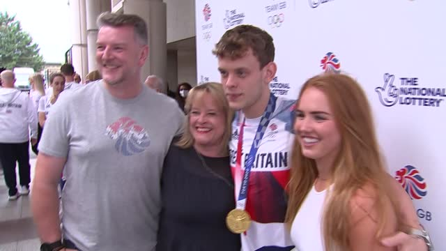 tokyo olympic games: team gb swimmers arrive at heathrow; england: london: heathrow airport: ext tom dean takes photo with fans showing off medals /... - gold coloured stock videos & royalty-free footage
