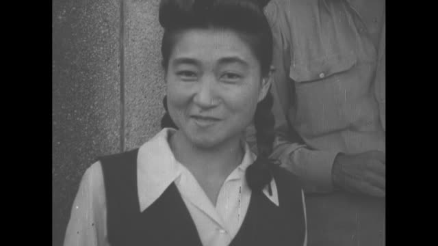 tokyo rose iva toguri d'aquino with smiling us military men / vs she exits wooden building in crowd of americans in khaki uniforms smiling with... - newsreel stock videos & royalty-free footage