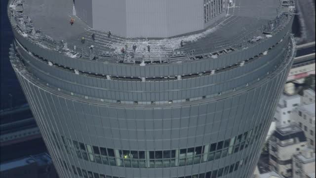vídeos de stock, filmes e b-roll de tokyo skytree maintenance workers remove snow from the observation deck roof. - ponto de observação