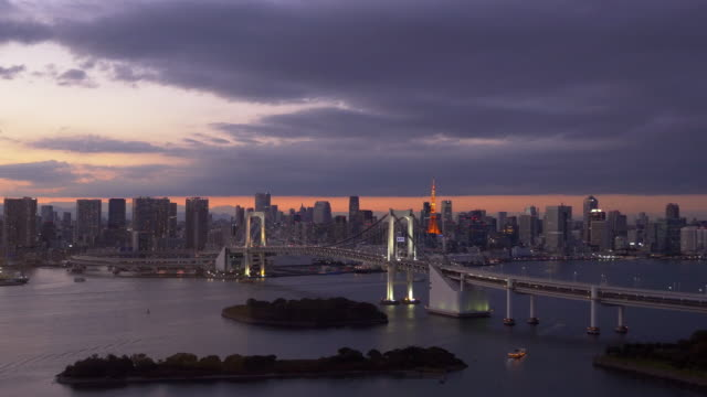 Tokyo tower and rainbow bridge light up at dusk