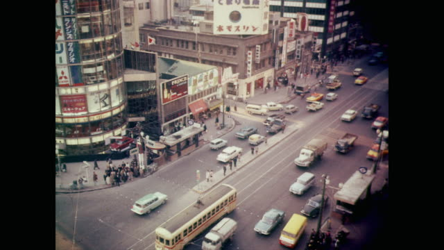 vídeos de stock, filmes e b-roll de 1964 tokyo traffic and pedestrians bustle along the ginza commercial district during the day - 1964