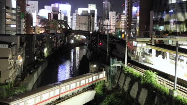 stockvideo's en b-roll-footage met tokyo treinen passeren van akihabara electric town's nachts - forensentrein