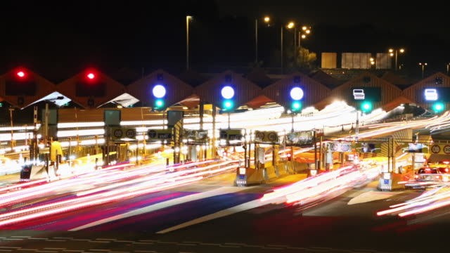 vídeos y material grabado en eventos de stock de toll at night in highway with long exposure light trail effect. - peaje