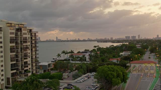 stockvideo's en b-roll-footage met tollgate op venetiaanse causeway, biscayne island, miami, florida, bij zonsopgang. luchtvideo met achterwaartse camerabeweging. - venetian causeway bridge