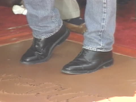vídeos de stock e filmes b-roll de tom cruise steps onto wet clay cement on his walk if fame space; on feet being imprinted in cement; tom rocking tilting feet forward & back to get... - tom cruise