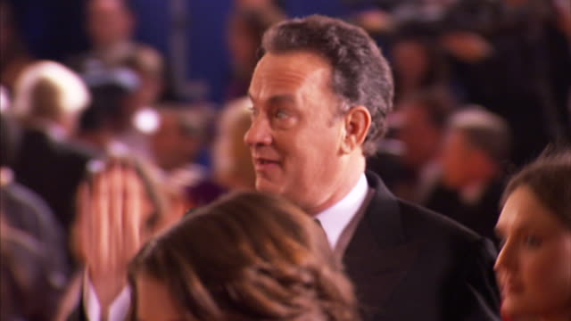 MCU Tom Hanks and Rita Wilson walking quickly down the red carpet