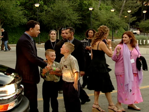Tom Hanks and Rita Wilson walks toward red carpet greeting children and fans along the way