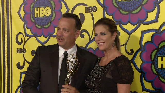 Tom Hanks holding Emmy award with Rita Wilson posing for paparazzi on the red carpet at Pacific Design Center