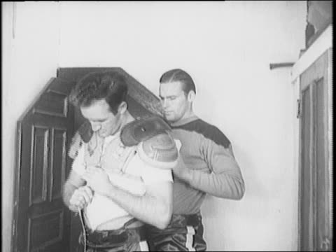 tom harmon and john kimbrough make professional debut in front of new york americans fans / harmon and kimbrough get dressed in the locker room,... - インターセプト点の映像素材/bロール