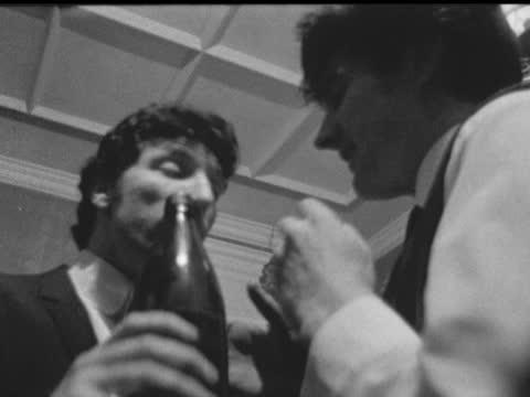 tom jones at party; wales: pontypridd: int side tom jones talking: tms party seen through chandelier: he holds disc av jones drinks out of beer... - beer bottle stock videos & royalty-free footage