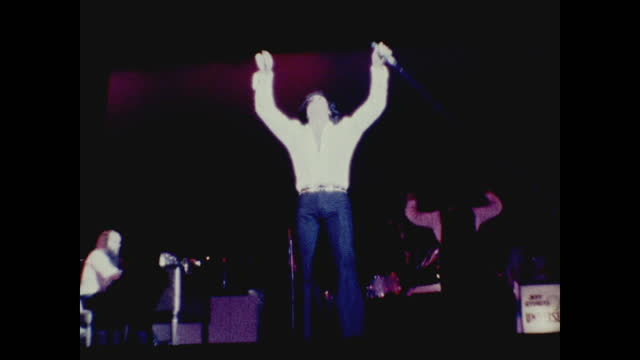 tom jones dancing and singing under the spotlight at the long beach amphitheater; band playing and lights flashing in the background - typisch walisisch stock-videos und b-roll-filmmaterial