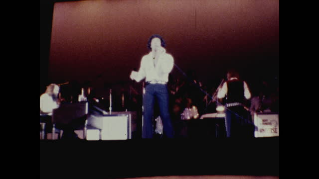 tom jones dancing hysterically on stage under the spotlight at the long beach amphitheater; band playing music in the background - typisch walisisch stock-videos und b-roll-filmmaterial