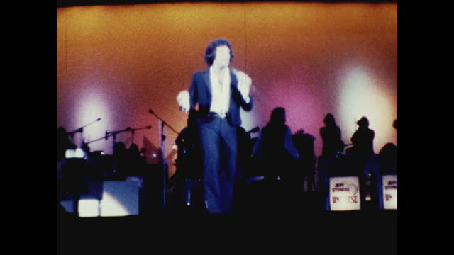 tom jones singing and dancing in front of band on stage at the long beach amphitheater; silhouette of the band against colorful lights - typisch walisisch stock-videos und b-roll-filmmaterial