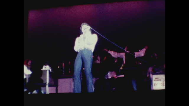 tom jones singing and dancing on stage with band playing behind him at the long beach amphitheater - typisch walisisch stock-videos und b-roll-filmmaterial