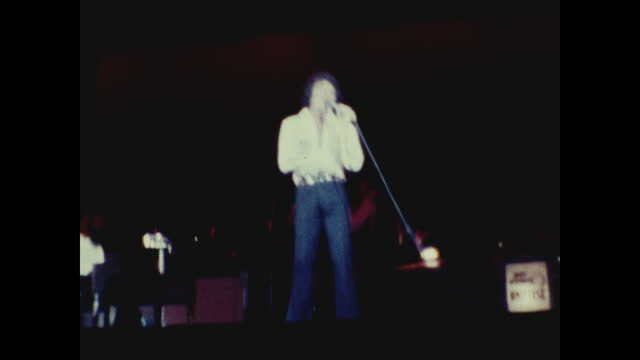 tom jones swinging his jacket in the air while singing and dancing on stage at the long beach amphitheater; pianist playing piano in the background - typisch walisisch stock-videos und b-roll-filmmaterial
