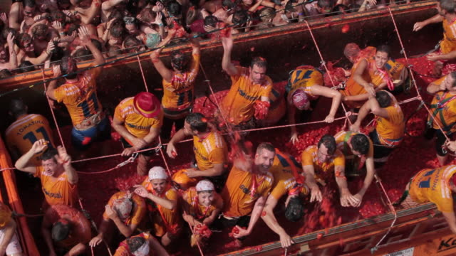 "stockvideo's en b-roll-footage met ""tomatina volunteers throw tomatoes form a truck on the street of buì±ol, valencia, spain."" - gooien"