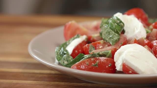 tomato basil salad with sliced mozzarella cheese - cucina vegetariana video stock e b–roll
