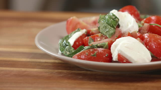 tomato basil salad with sliced mozzarella cheese - salad stock videos & royalty-free footage