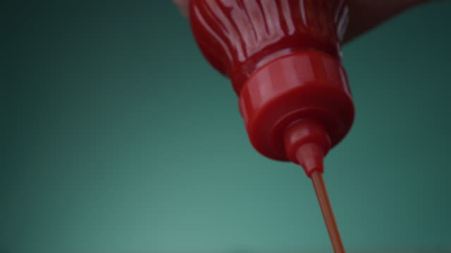 tomato ketchup is squeezed from a red bottle a closeup on a biscay green aqua menthe color background - sauce stock videos & royalty-free footage