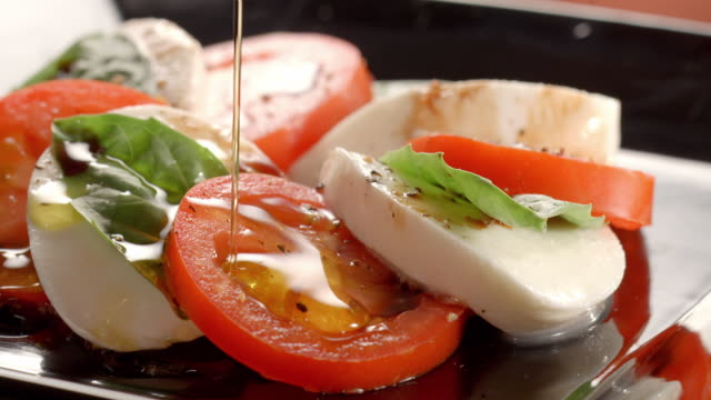 vídeos y material grabado en eventos de stock de ecu tomato mozzarella salad with basil on a rotating salad plate as virgin olive oil is poured over salad - ensalada