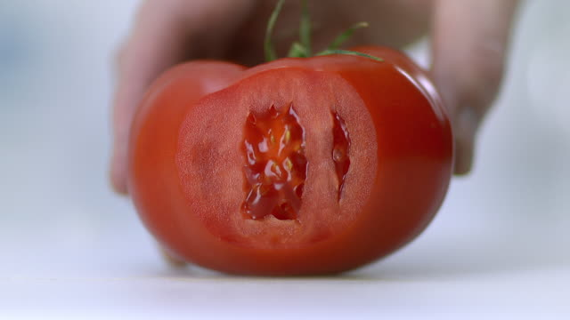 A tomato placed on a white chopping board being held by hand and sliced very finely