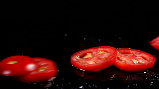 slo mo tomato slices falling down on wet surface - chopped food stock videos and b-roll footage
