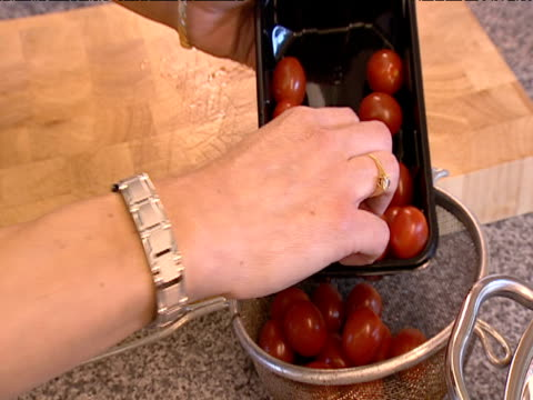 Tomatoes are poured into sieve ready for washing