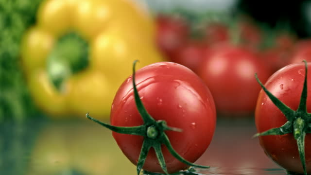 vídeos de stock e filmes b-roll de slo mo tomatoes rolling on a table - rolar