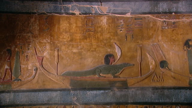 tomb of seti i. wide of painted bas-relief of a crocodile in a boat on the nile river. - basrelief stock-videos und b-roll-filmmaterial